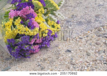 Bouquet of violet yellow pink and white statis on the sand