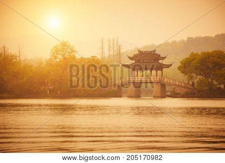 Traditional style pavilion and bridge at XiHu West Lake at sunset, Hangzhou, China
