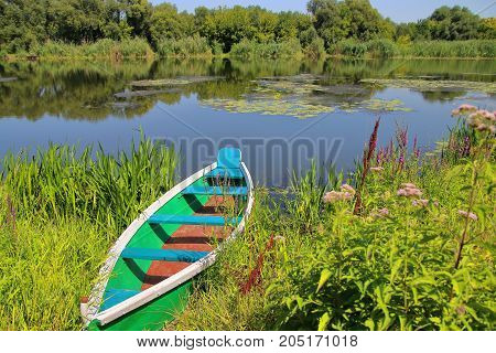 The picture was taken in Ukraine on the South Bug river. In the picture a fishing boat moored to the river bank.
