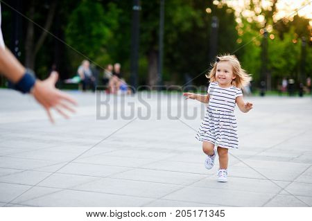 Adorable little girl runs towards the parent hands. Warm summer day. Baby is very fun.