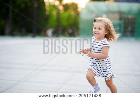 Cute little girl runs around the square in a city park. Warm summer day. Baby is very fun.