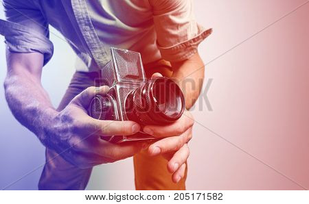Fashion Photographer with old film camera in hand while working in studio. tinted in red and blue.