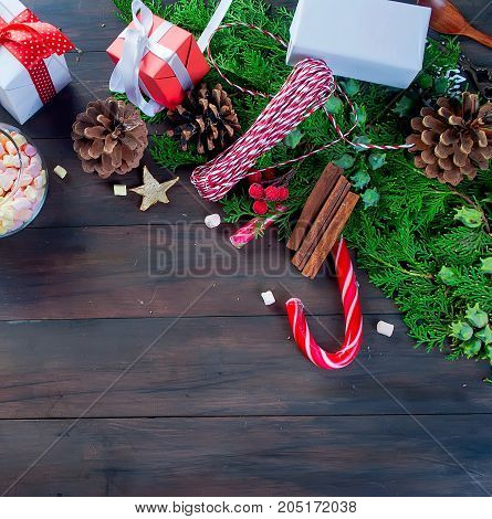 Christmas traditional hot drink cocoa in red cup cocoa powder in a jar fir branches and bumps cones on the dark wooden background Christmas evening Christmas card Holiday Concept Top view copy space