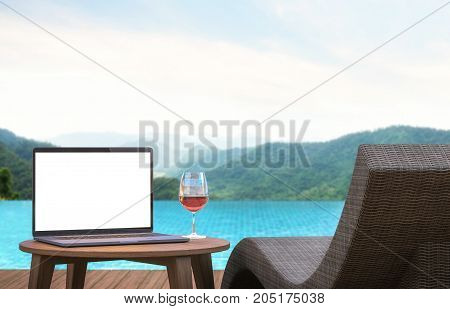 Blank laptop monitor and poo lbed 3d rendering image.An empty laptop screen is placed on a table by the pool. focus at laptop monitor. There are mountain and nature scenes with blurry background