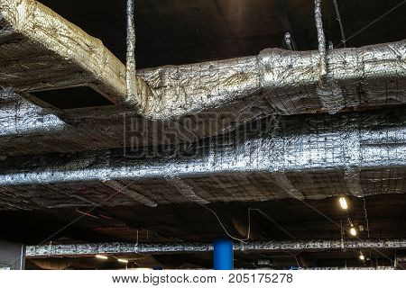large tin ventilation pipes on the ceiling