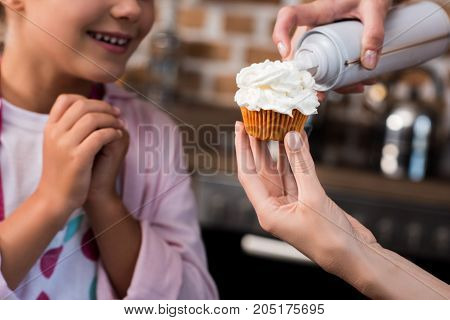 Woman Putting Buttercream On Cupcake