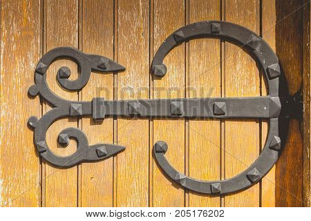 on a church very big iron hinge forged on a wooden door to the used paint