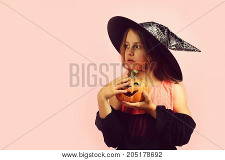 Girl With Carved Orange Pumpkin Isolated On Pink Background