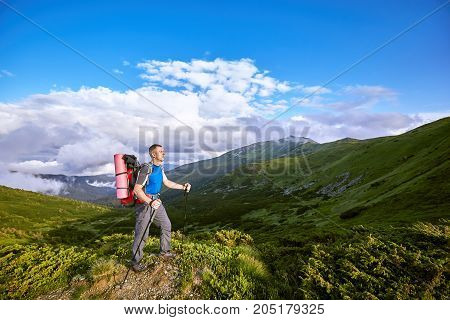 Hiking in the mountains with a backpack in the summer.