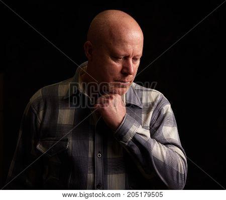 Sad Senior Man Looking Down And Thinking