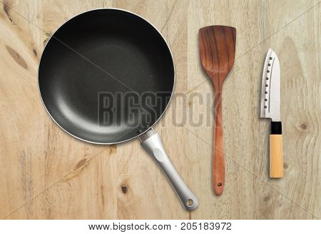 Top View frying and pan spatula and knife on the wooden background.