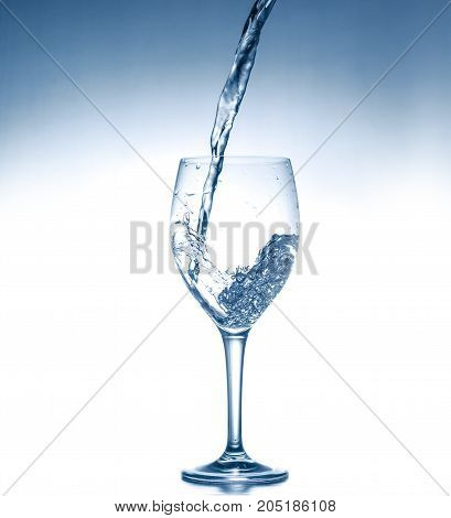 Water in wineglass on white and blue background