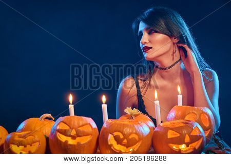Beautiful witch with Halloween pumpkins over blue background with backlight looking to the side at blank copy space