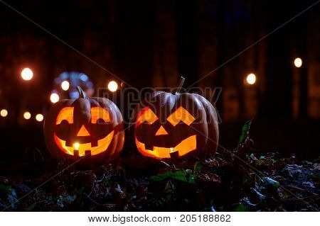 Two Halloween Pumpkins in the park at night