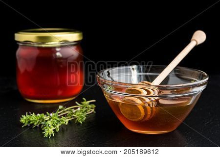 Honey in glass bowl and jar with wooden honey dipper on black dish