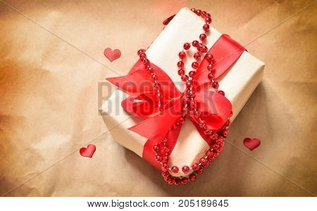gift box with a red heart on a brown old table. Valentine day.