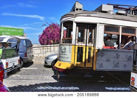 Lisbon Portugal - June 11 2017: lisbon traffic. Vintage yellow tram on a narrow street of romantic old Alfama