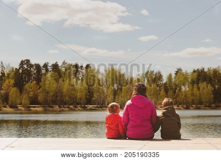 mother with two kids looking at autumn nature, autumn family activities