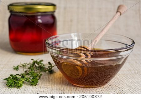 Honey in glass bowl and jar with wooden honey dipper on natural matting