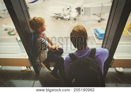 family travel- father and son looking at planes in the airport