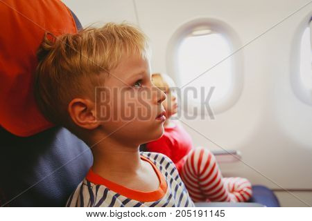 little boy and girl watch tv or flight safety in plane, kids and family travel