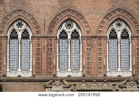 Bologna (Emilia Romagna Italy): facade of historic building in a sunny morning. Three windows