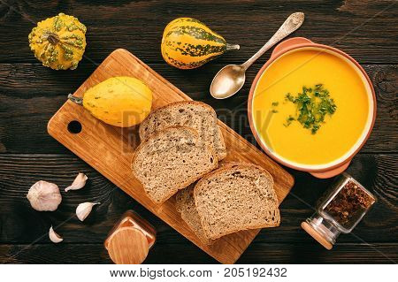 Homemade pumpkin cream soup on black background.