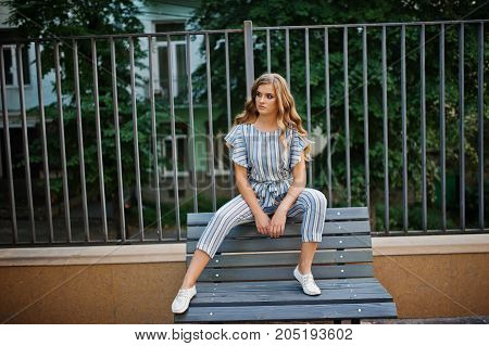 Fabulous Young Attractive Model In Striped Overall Sitting On A Bench Outdoor With Trees On The Back