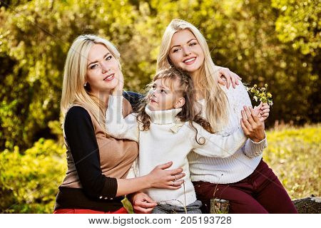 Portrait of three happy smiling sisters having fun on sunny day