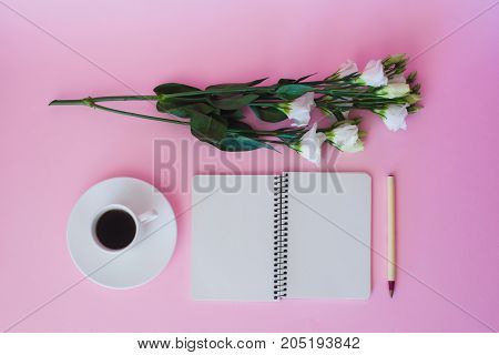 Top view of blank notebook pen branch of flowers and cup of coffee over pink background.