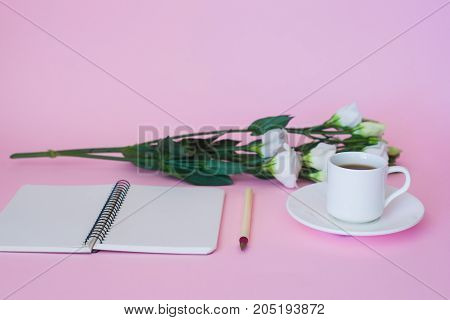 Front view of blank notebook pen branch of flowers and cup of coffee over pink background.