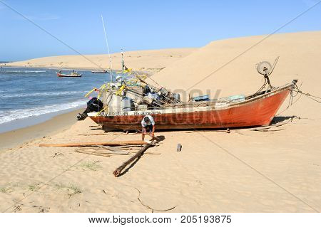 Barra de Valizas Uruguay - 11 february 2011: fisherman working at his boat on the beach of Barra de Valizas in Uruguay
