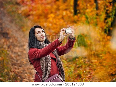 Attractive happy woman making selfie in autumn park