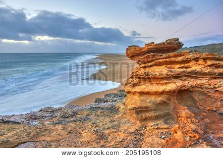 Rocks and waves of surf in the ocean near Farol De Nazare coast, in vicinity of Nazare, Portugal