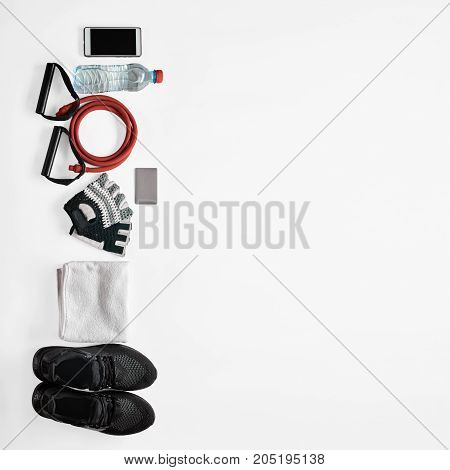 Smartphone, drinking water, resistance band, gloves, towel and gymshoes on white background, image with Square ratio