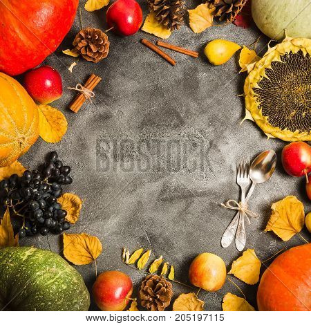 Autumn concept from fallen leaves and fruits with vintage place setting on old table. Thanksgiving day background, Flat lay, top view