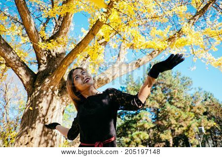 Happy young woman in park on sunny autumn day smiling. Cheerful beautiful girl in black retro dress autumn fashion style