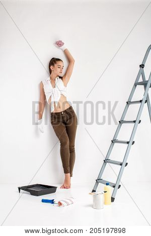 beautiful sexy woman painting a wall in her house