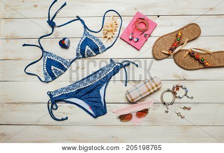 Flat lay of summer fashion with blue bikini swimsuit inside the bag and other girl accessories on white wooden background
