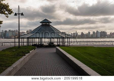 A gazebo in Hoboken's Sinatra Park by the Hudson River with the New York skyline in the background.