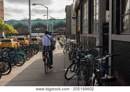 Hoboken NJ USA -- September 19 2017 A cyclist heads toward the Hoboken train station through a lane of other bicycles parked on either side. Editorial Use Only.