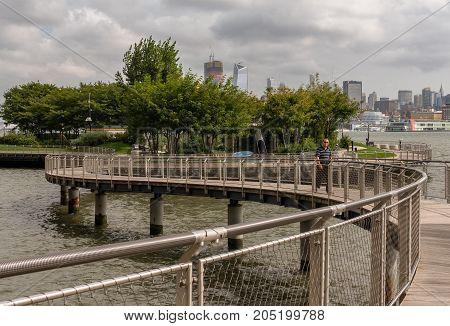 Hoboken NJ USA -- September 19 2017 --Man walks along a winding waterfront walkway in Hoboken. Editorial Use Only.
