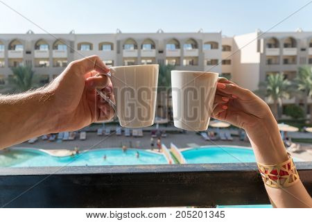 The Hands Of Men And Women Keep Coffee Mugs On The Balcony In The Background Of The Hotel, Where The