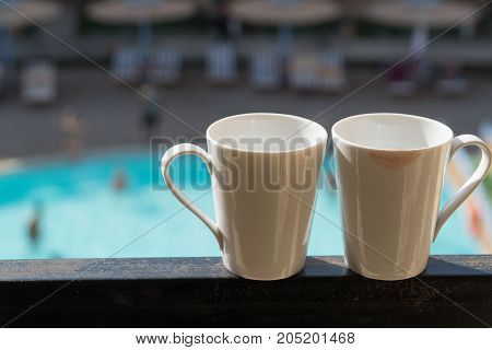 Two White Mugs Stand On The Balcony In The Background Of The Hotel, Where The Buildings And The Pool