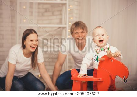 Lovely Baby Boy In Santa Claus Costume For Christmas. Mother, Father And Little Son Playing. Happy F