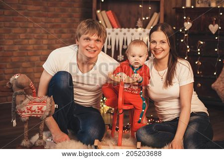 Lovely Baby Boy In Santa Claus Costume For Christmas. Mother, Father And Little Son Playing.