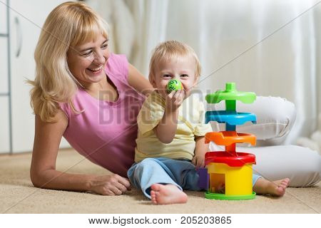 Mom and child with colorful logical toy. Family having a fun playing together at home.