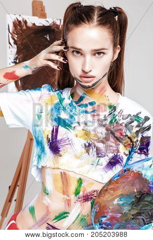 beautiful young woman artist soiled in colorful paint  holding a pallet.  face is stained with paint