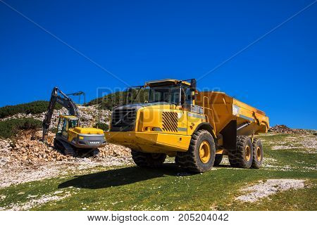 VOGEL MOUNTAIN SLOVENIA - AUGUST 30 2017: Construction machinery for crushing stone Volvo bulldozer and large truck dumper working on mountain