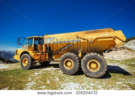 VOGEL MOUNTAIN SLOVENIA - AUGUST 30 2017: Construction machinery for crushing stone large Volvo truck dumper working on mountain